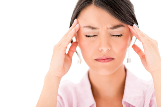 Frustrated woman having a headache - isolated over a white background