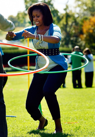 WASHINGTON - OCTOBER 21:  U.S. first lady Michelle Obama hula hoops on the South Lawn of the White House during an event promoting exercise and healthy eating for children October 21, 2009 in Washington, DC. The Healthy Kids Fair included events on cooking healthy meals and emphasized children getting a proper amount of outdoor exercise each day.  (Photo by Win McNamee/Getty Images)
