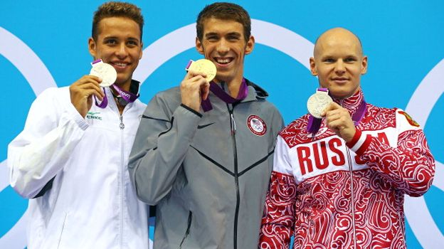 LONDON, ENGLAND - AUGUST 03: Silver medallist Chad le Cos of South Africa, gold medallist Michael Phelps of the United States, and silver medallist Evgeny Korotyshkin of Russia pose on the podium during the medal ceremony for the Men's 100m Butterfly Final on Day 7 of the London 2012 Olympic Games at the Aquatics Centre on August 3, 2012 in London, England.  (Photo by Al Bello/Getty Images)