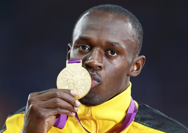 Jamaica's Usain Bolt kisses his gold medal during the men's 100m victory ceremony during the London 2012 Olympic Games at the Olympic Stadium August 6, 2012.         REUTERS/Eddie Keogh (BRITAIN  - Tags: OLYMPICS SPORT ATHLETICS TPX IMAGES OF THE DAY)