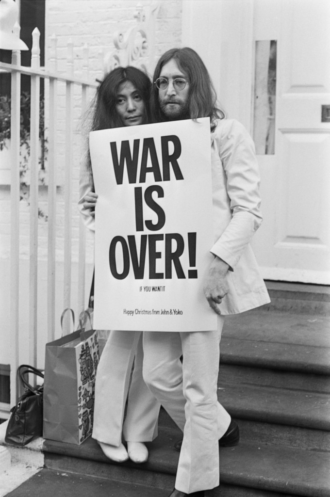 John Lennon (1940 - 1980) and Yoko Ono pose on the steps of the Apple building in London, holding one of the posters that they distributed to the world's major cities as part of a peace campaign protesting against the Vietnam War, December 1969. The poster reads 'War Is Over, If You Want It'. (Photo by Frank Barratt/Keystone/Getty Images)